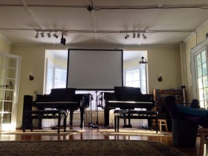 Living room pianos with overhead screen for music. Photo by Todd Pinter